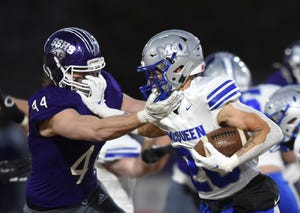 McQueen's Ashton Hayes stiff arms Spanish Springs' Luke Stuber as he carries the ball during Friday's game at Spanish Springs on March 12, 2021. McQueen went on to win 26-20.