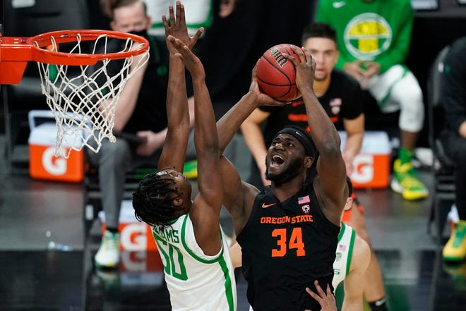 Oregon State's Rodrigue Andela (34) shoots over Oregon's Eric Williams Jr. (50) during the first half of an NCAA college basketball game in the semifinal round of the Pac-12 men's tournament Friday, March 12, 2021, in Las Vegas.