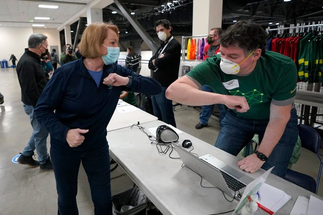 Seattle Mayor Jenny Durkan, left, greets a worker at a volunteer check-in station, Saturday, March 13, 2021, on the first day of operations at a mass COVID-19 vaccination site at the Lumen Field Events Center in Seattle, which adjoins the field where the NFL football Seattle Seahawks and the MLS soccer Seattle Sounders play their games.