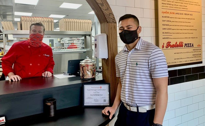Mike Haran, left, opened I Fratelli Pizza in Westlake on March 8, and welcomed customer Jacob Ledesma, who endorsed the fresh, thin crust oblong pizza served in the take-out restaurant that offers free delivery in the area.