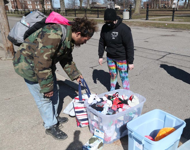 Kimberly Stimmel, right, talks with Christian on Sunday as he looks over donated clothing Stimmel is providing to homeless men at Grace Park in Akron as part of her charitable group called Closet of Caring.