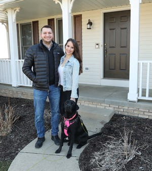 Sam and Ashley Myers stand with their dog, Lily, in front of their new home in Copley. The couple toured more than 100 Greater Akron houses for sale and put in solid offers on 11 —10 were over the seller's asking price by as much as $25,000.