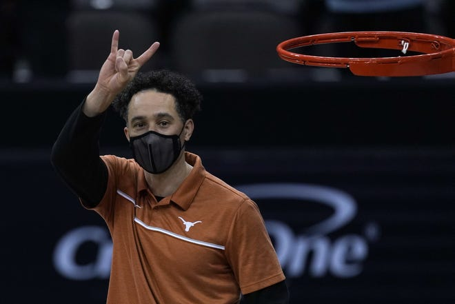 Texas head coach Shaka Smart motions to the crowd after winning their NCAA college basketball game against Oklahoma State for the Big 12 tournament championship in Kansas City, Mo, Saturday, March 13, 2021.