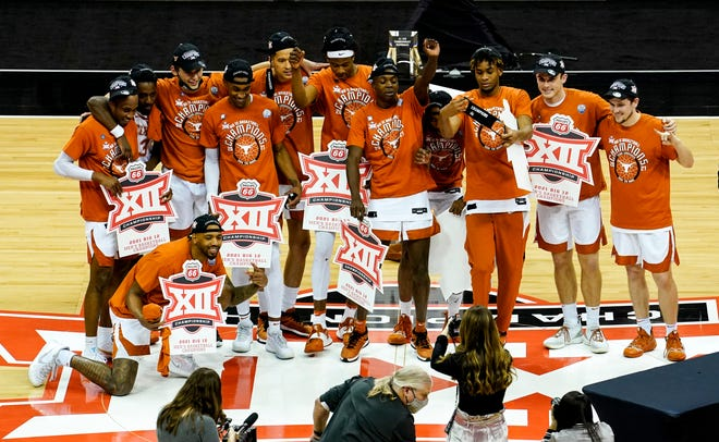 Mar 13, 2021; Kansas City, MO, USA; The Texas Longhorns pose for a photo after winning the Big 12 Conference Tournament Championship against the Oklahoma State Cowboys at T-Mobile Center.