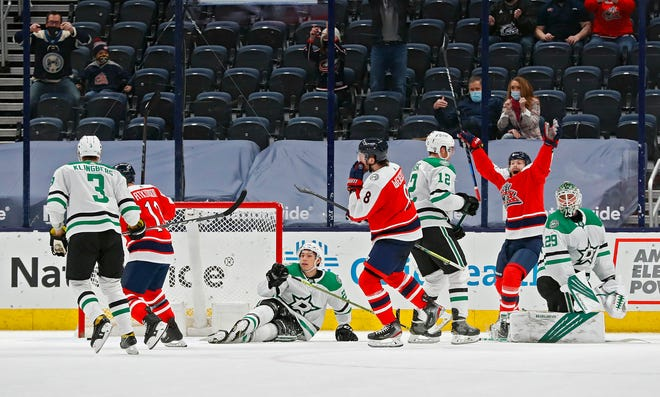 Zach Werenski (8) scores the game winning goal in overtime against Dallas Stars on Saturday night at Nationwide Arena, lifting the Blue Jackets to a 4-3 victory.
