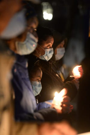 From left, Betsy Donovan, Marina Flores, 9, and Tiesha Flores during a candlelight vigil commemorating the one-year anniversary of the COVID-19 pandemic lockdown on Saturday, March 13, 2021, at Central Square in Bridgewater. The evening honored the lives of long-term care residents who lost their battle to COVID-19 and celebrated the resilience of survivors.