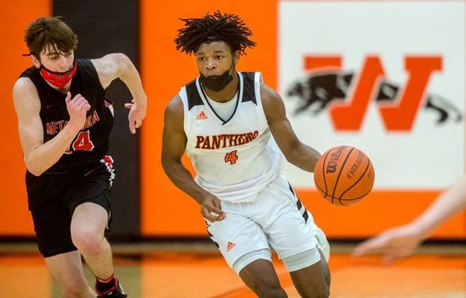 Washington's Drew Lewis (4) moves the ball up the court past Metamora's Drew Tucker in the second half of the Mid-Illini Conference title game Saturday, March 13, 2021 in Washington. The Panthers defeated the Redbirds 69-52 for the title.