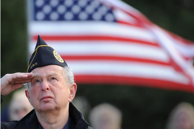 Larry Herson salutes the flag during the playing of the national anthem at a 2010 Veterans Day event.