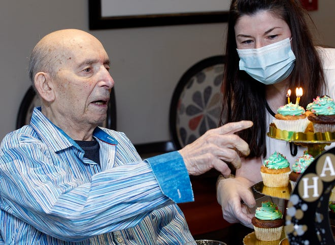 Activity Director Judy Conenberg brings over cupcakes for David Levenson to choose as he celebrates his 103d birthday at The Brookdale Cushing Park Senior Living Community in Framingham.