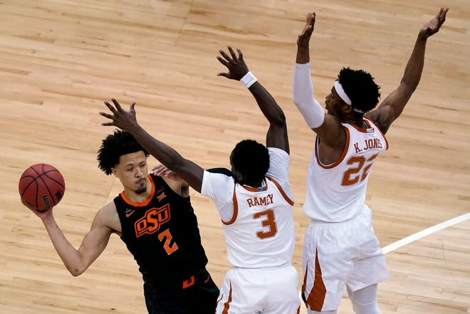 Oklahoma State's Cade Cunningham looks to pass under pressure from Texas' Kai Jones (22) and Courtney Ramey (3) during the first half of the Longhorns' 91-86 win Saturday for the Big 12 title in Kansas City, Mo.