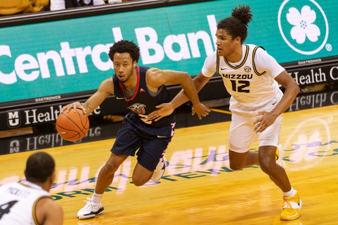 Liberty's Darius McGhee, left, drives past Missouri's Dru Smith, right, during the first half of game on Dec. 9 in Columbia, Mo.