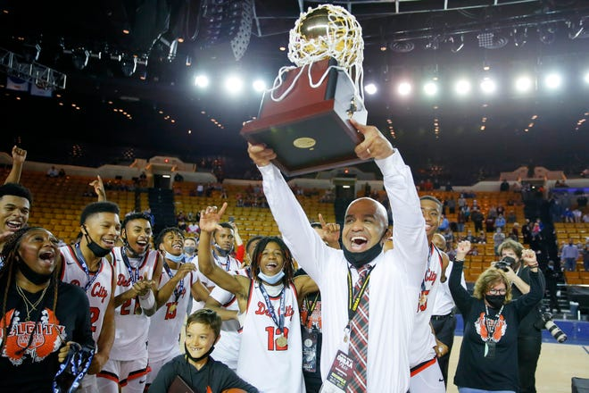 Del City coach Lenny Hatchett hoists the Class 6A state championship trophy Saturday night at the Mabee Center in Tulsa.