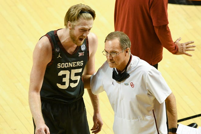 Oklahoma forward Brady Manek (35) talks with head coach Lon Kruger during a timeout on March 1 at Oklahoma State.