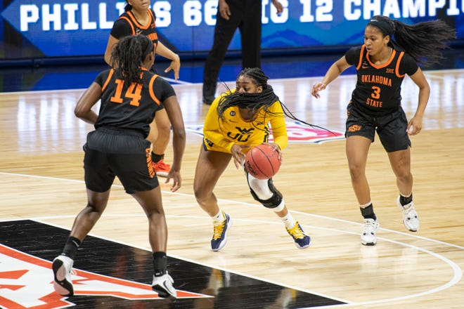 West Virginia guard Jayla Hemingway (0) dribbles through Oklahoma State defenders in the second half of a 59-50 win in the Big 12 women's basketball tournament semifinals Saturday at Municipal Auditorium in Kansas City, Mo.