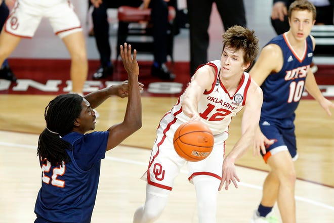 Oklahoma's Austin Reaves (12) passes the ball around UTSA's Keaton Wallace (22) during a Sooner win on Dec. 3 at Lloyd Noble Center in Norman.