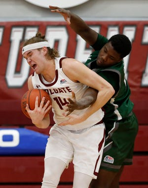 Colgate's Keegan Records grabs a rebound in front of Loyola's Golden Dike during Patriot League championship game on Sunday in Hamilton, N.Y. The Raiders won, 85-72.  Records, a South Kingstown native, will be one of only two players from Rhode Island who will be going to the NCAA basketball tournament. The other is Portsmouth's Cole Swider with Villanova.