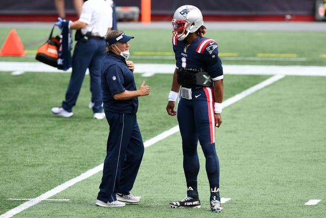 Patriots head coach Bill Belichick talks with quarterback Cam Newton before the game against the Miami Dolphins on Sept. 13 at Gillette Stadium. Newton has signed on for a second season with New England.