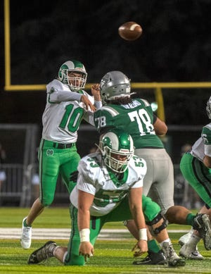 St. Mary's quarterback Cruz Herrera throws a pass during a varsity football game at De La Salle High School in Concord on March 13.