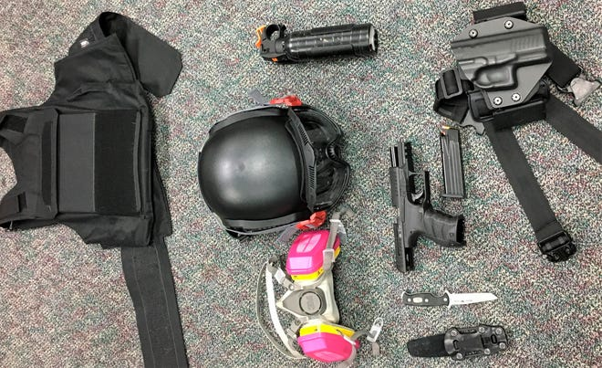 This photo released by Portland Police Bureau shows numerous items left behind by people inside the perimeter of a march after they corralled a group of about 100 protesters Friday night in Portland. On Saturday police said officers surrounded protesters about 15 minutes after the march began in the city's Pearl District at 9 p.m. because some began smashing windows.