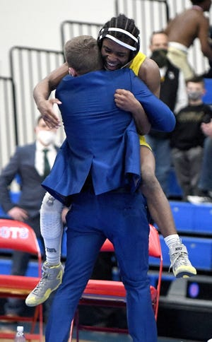Kyren Butler of Copley jumps into his coach Josh Tomayko's arms after defeating Pablo Castro of Louisville for the Division II 132-pound state championship.[Kevin Whitlock/IndeOnline.com]