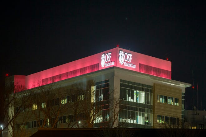 Pink lights illuminate the exterior of OSF HealthCare Saint Anthony Medical Center Saturday, March 13, 2021, in Rockford, to mark the one-year anniversary of the COVID-19 pandemic.