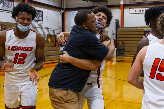 Lanphier boys basketball head coach Blake Turner celebrates with Lanphier's Tye Banks Jr. (2) after the Lions defeated Decatur MacArthur in the Central State Eight Conference Boys Basketball Tournament championship game at Lober-Nika Gymnasium on Saturday. [Photo by Jason Johnson]