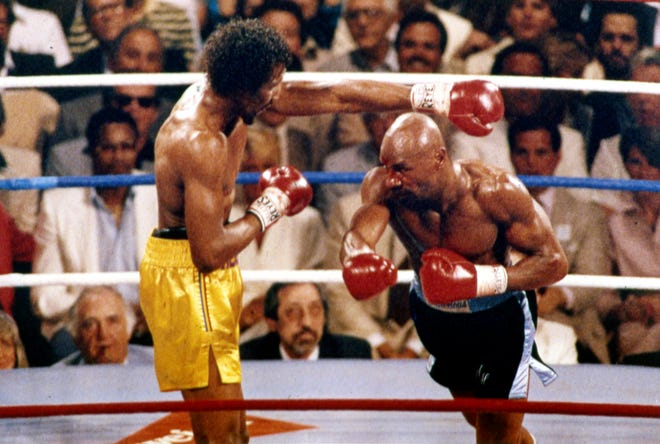 """FILE - In this April 1985 file photo, Marvin Hagler, right, and Thomas Hearns fight during the first round of a world championship boxing bout in Las Vegas. Hagler, the middleweight boxing great whose title reign and career ended with a split-decision loss to """"Sugar"""" Ray Leonard in 1987, died Saturday, March 13, 2021. He was 66."""