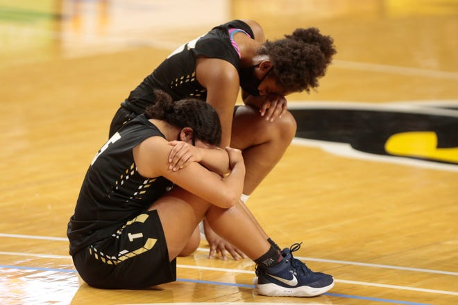 Topeka High seniors Lilly Smith and Ja'Neysha Hendricks sit down at midcourt following the Trojans' 61-54 loss to Shawnee Mission Northwest on Saturday during the Class 6A state championship game at Koch Arena in Wichita.
