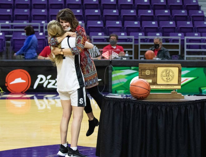 Sterling junior Kali Briar picks up her coach Jill Rowland on Saturday after winning the Class 2A state basketball championship. Sterling defeated Colgan 52-36 at Bramlage Coliseum.