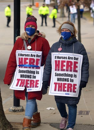 Nurses walk the picket line on Bridge Street near the staff entrances to St. Vincent Hospital on Sunday in Worcester.