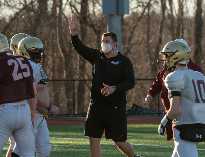 Shepherd Hill Regional assistant football coach Chris Lindstrom, center, runs through a play with the team during a recent practice in Dudley.