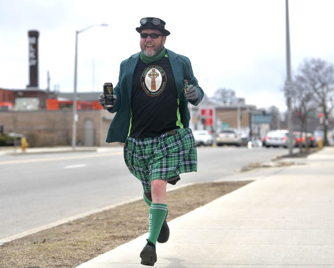 WORCESTER - Holding a can of Guinness in one hand and a shot of whiskey in the other, Dave Hanson jogs the parade route of the Worcester County St. Patrick's Parade along Park Avenue on Sunday. The annual event was canceled again this year due to the pandemic.