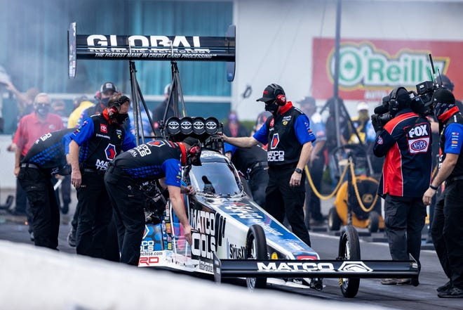 Mechanics make final adjustments on a Top Fuel vehicle Sunday during the AMALIE Motor Oil NHRA Gatornationals at Gainesville Raceway.