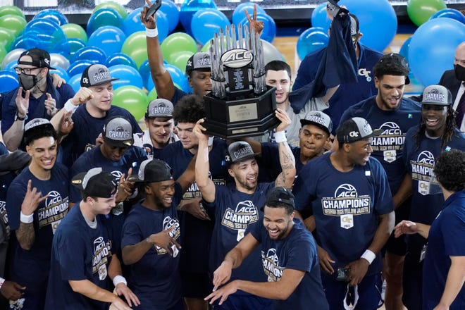 Jose Alvarado holds the ACC Tournament championship trophy while surrounded by Georgia Tech teammates Saturday night at the Greensboro Coliseum.
