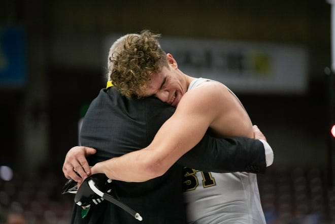 East High School's Xavier Freeman hugs head coach Pat Laughlin after winning the Class 4A 182-pound championship at the Southwest Motors Events Center on Saturday March 13, 2021.