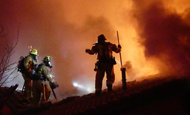 Apple Valley Fire Protection District firefighters battle a house fire from the roof in Apple Valley on Saturday, March 13, 2021. No one was injured and several dogs were rescued at the scene.