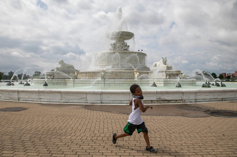 Jayden Poe, 5, of Detroit, runs around the James Scott Memorial Fountain that opened officially on Belle Isle on May 29, 2020.
