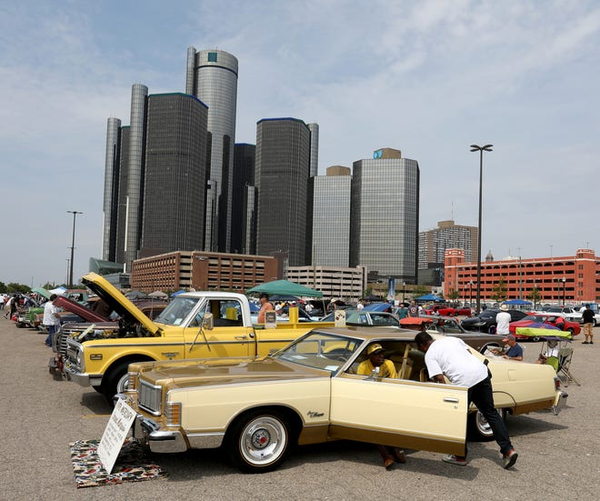 """People check out all kinds of cars including this 1976 Mercury Grand Marquis during the """"Chief James E. Craig Detroit Police Department Presents Showdown in Motown Bike and Car Show Extravaganza on Atwater Street near the Riverwalk in Detroit, Michigan on July 14, 2018. Over 100 cars and motorcycles were on display with trophies going to winners after the judging was over."""