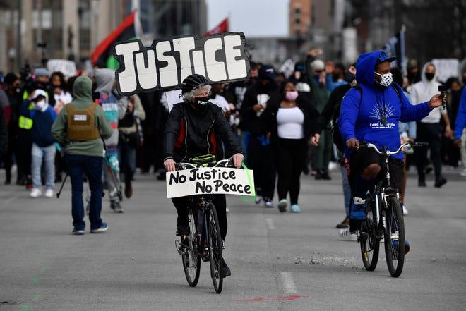 Seorang pengendara sepeda memimpin sekelompok pengunjuk rasa di Jefferson Street di Louisville, Ky., Pada peringatan satu tahun kematian Breonna Taylor pada hari Sabtu, 13 Maret 2021.