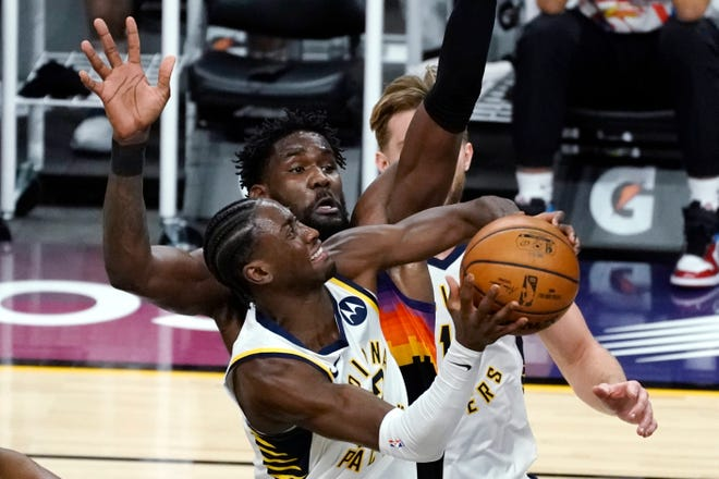 Indiana Pacers guard Caris LeVert (22) drives past Phoenix Suns center Deandre Ayton (22) during the first half of an NBA basketball game Saturday, March. 13, 2021, in Phoenix. (AP Photo/Rick Scuteri)