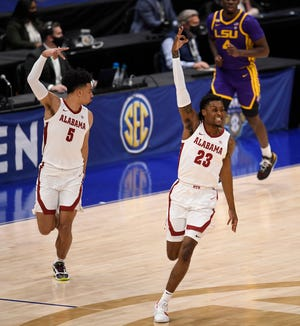Alabama guard Jaden Shackelford (5) and guard John Petty Jr. (23) celebrate a three point basket during the first half of the SEC Men's Basketball Tournament Championship game at  Bridgestone Arena Sunday, March 14, 2021 in Nashville, Tenn.