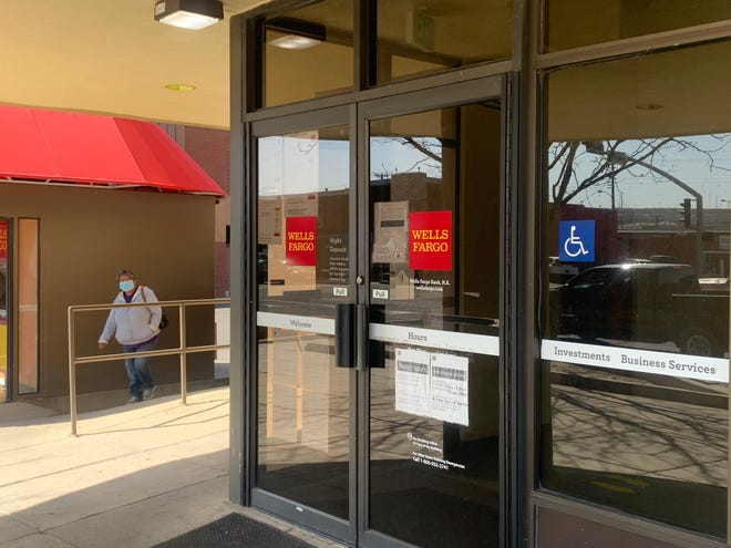A person approaches the Wells Fargo Bank main branch  at 100 E. Broadway Ave. in Farmington on the afternoon of March 12, 2021. The branch will shut down at noon on Wednesday, June 2, 2021.