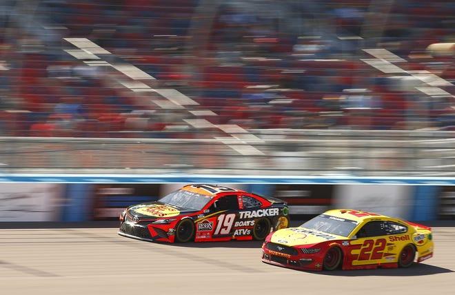 Martin Truex Jr. (19) and Joey Logano (22) battle for position at Phoenix Raceway.