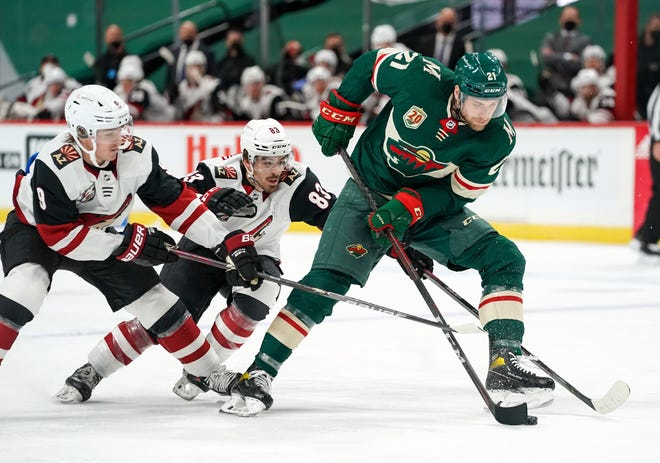 Mar 14, 2021; Saint Paul, Minnesota, USA; Minnesota Wild defenseman Carson Soucy (21) protects the puck from Arizona Coyotes right wing Clayton Keller (9) and right wing Conor Garland (83) during the second period at Xcel Energy Center. Mandatory Credit: Nick Wosika-USA TODAY Sports