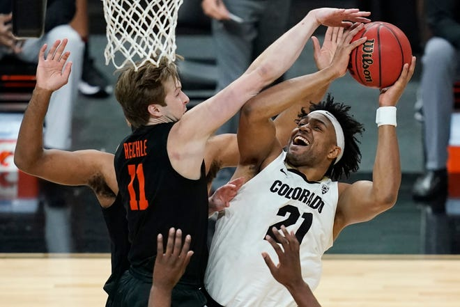 Colorado's Evan Battey (21) shoots around Oregon State's Zach Reichle (11) during the first half of an NCAA college basketball game in the championship of the Pac-12 men's tournament Saturday, March 13, 2021, in Las Vegas.