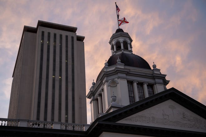 The sun sets behind the Florida Capitol Complex Wednesday, March 10, 2021.