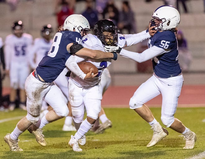 Central Valley Christian's Josh Sousa, left and Jj Hilvers take down Mission Oak quarterback Michael Iriye on Saturday, March 13, 2021 in the first officially sanctioned high school football game in Tulare County since the pandemic.