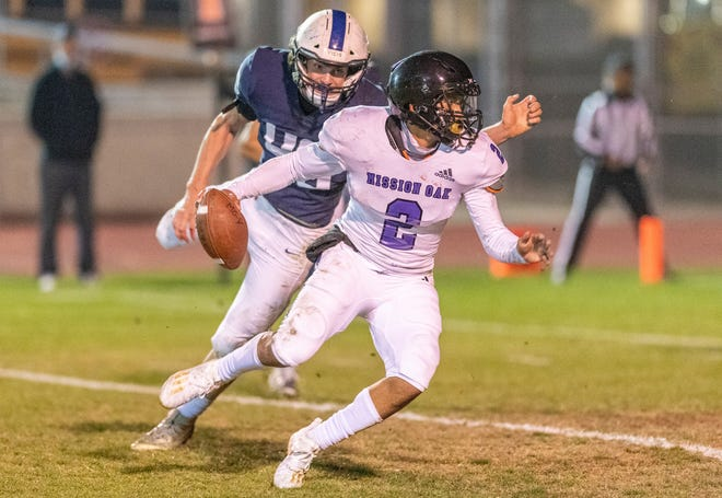 Mission Oak's Michael Iriye looks to pass under pressure from Central Valley Christian's Josh Sousa on Saturday, March 13, 2021 in the first officially sanctioned high school football game in Tulare County since the pandemic.