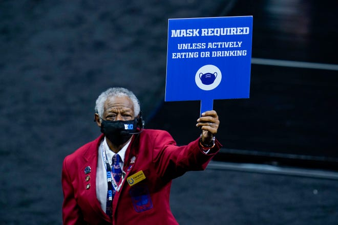 An usher holds a sign instructing fans to wear masks during an NCAA college basketball game at the Big Ten Conference tournament in Indianapolis.