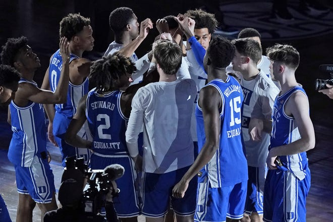 Duke players gather prior to the start of an NCAA college basketball game against Louisville in the second round of the Atlantic Coast Conference tournament in Greensboro, N.C.